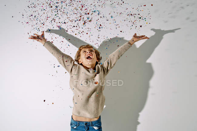 Joyful boy in casual clothing laughing while throwing colorful confetti with white wall on background — Stock Photo