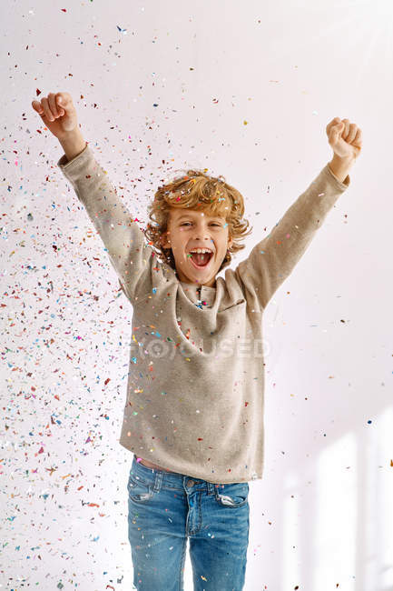 Overjoyed boy having fun with confetti at home — Stock Photo