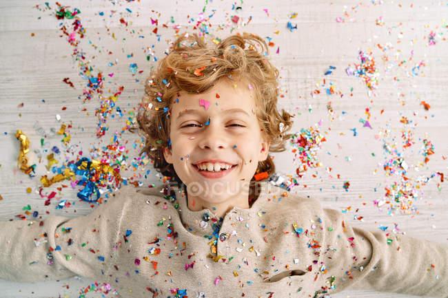Bellissimo ragazzo con il viso coperto di coriandoli — Foto stock