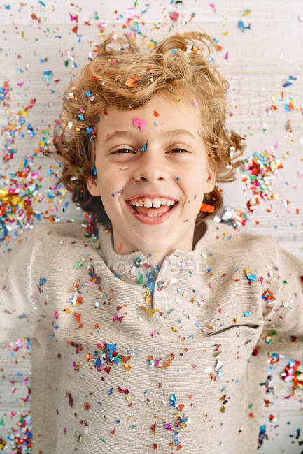 Beautiful boy with face covered in confetti — Stock Photo