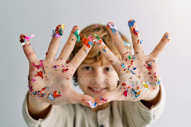 Удовлетворенный мальчик улыбается, демонстрируя руки в красочных конфетти на фоне белой стены — стоковое фото