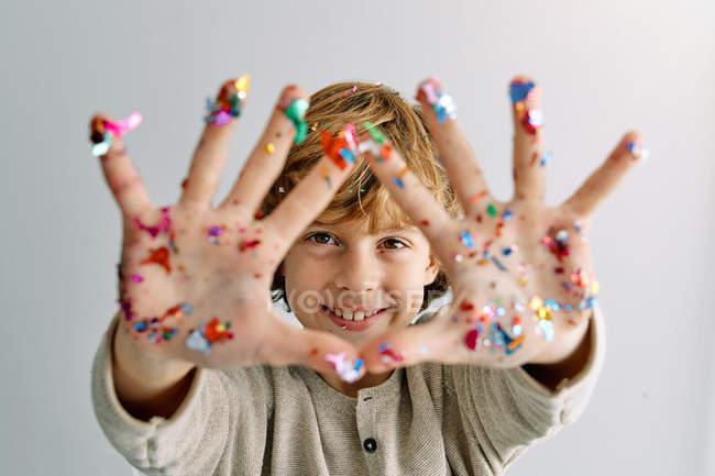 Содержательный мальчик показывает руки в конфетти — стоковое фото