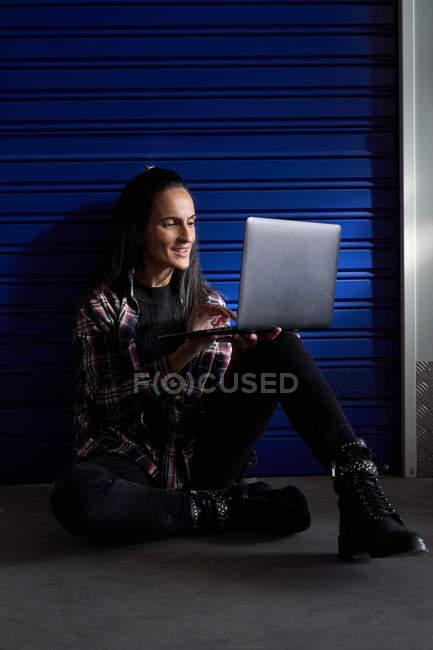 Молода жінка в шовковій сорочці сидить перед дверима комори і за допомогою ноутбука. — стокове фото
