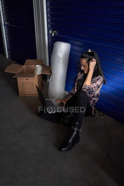 Жінка сидить на бетонній підлозі в самозберіганні на складі і за допомогою комп