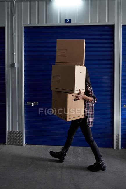 Женщина с картонными коробками в комнате самохранения — стоковое фото