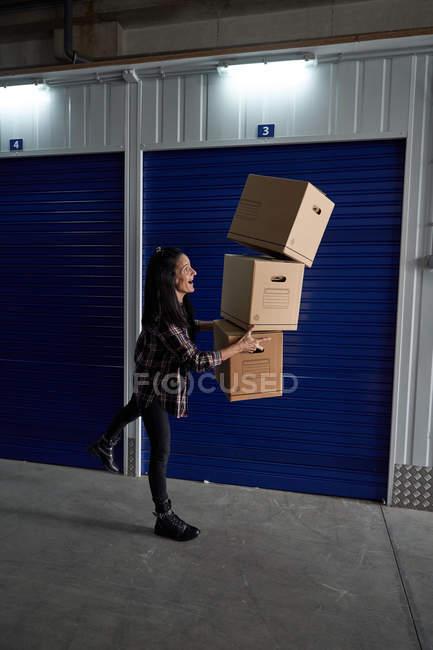 Jeune femme brune jouant comme portant des boîtes en carton dans une salle de stockage de soi — Photo de stock