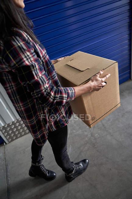 Recadré de femme portant boîte en carton dans un self-stockage — Photo de stock
