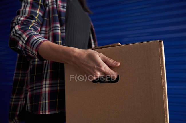 Мидсекция женщины, несущей картонную коробку в комнате самохранения — стоковое фото