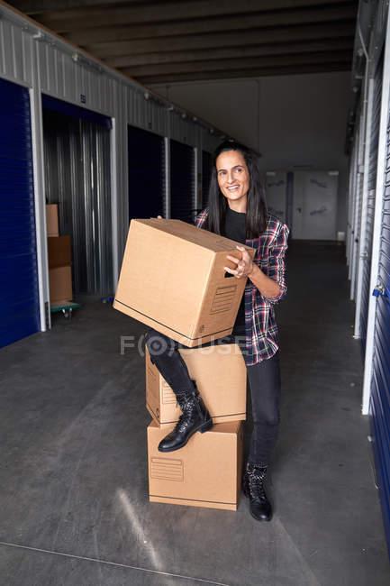 Belle femme assise sur des boîtes dans un bâtiment de self-stockage regardant loin — Photo de stock