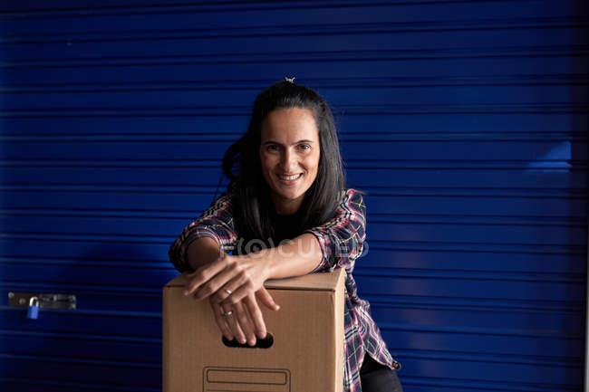 Женщина с коробкой для доставки смотрит в камеру в здании для хранения вещей — стоковое фото