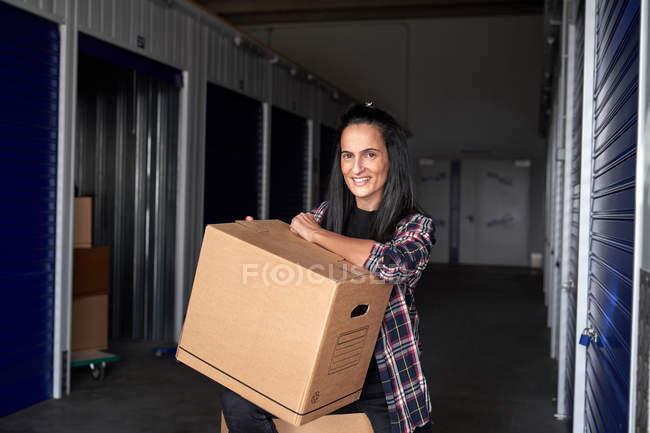 Курьер-женщина несет коробки и смотрит в камеру в здании самохранения — стоковое фото