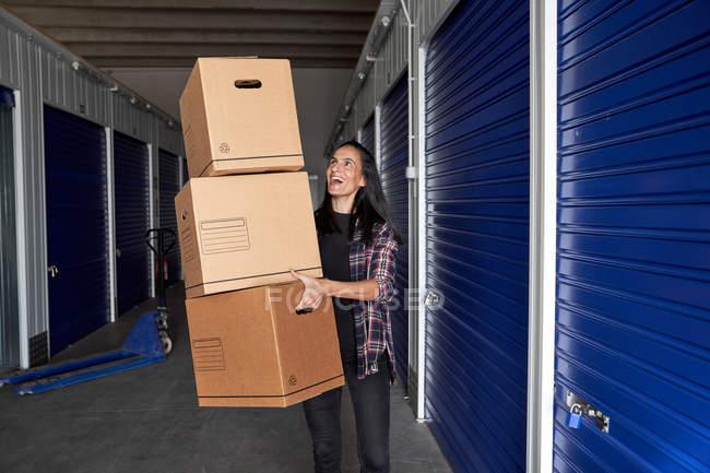 Счастливая взволнованная брюнетка с картонными коробками на складе — стоковое фото