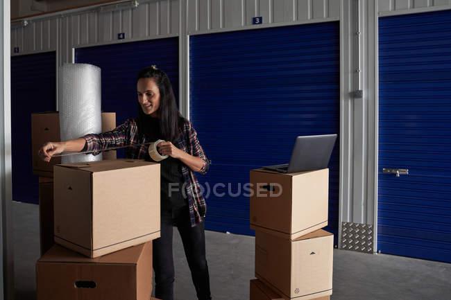 Женщина закрывает картонные коробки плотной лентой в коридоре самохранения — стоковое фото