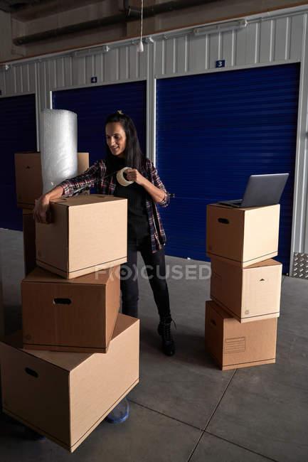 Cajas de cartón móviles con cinta adhesiva en un pasillo de autoalmacenamiento. - foto de stock