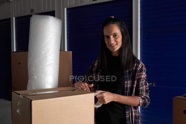 Женщина закрывает движущиеся картонные коробки с изолентой в коридоре самохранения, глядя в камеру — стоковое фото