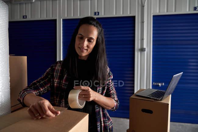 Женщина закрывает движущиеся картонные коробки с изолентой в коридоре самохранения — стоковое фото