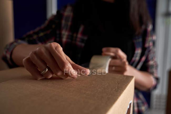 Руки женщины закрывают движущуюся картонную коробку плотной лентой, крупным планом — стоковое фото