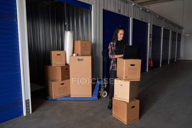 Жінка працює з ноутбуком у сховищі, організовує скриньки на складі самообслуговування. — стокове фото