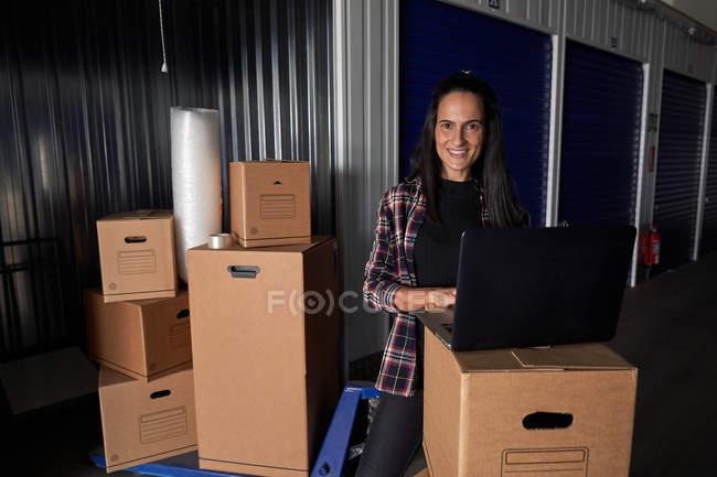 Жінка з ноутбуком, яка дивиться в камеру в рухомій сховищі, як організація ящиків на складі самообслуговування. — стокове фото