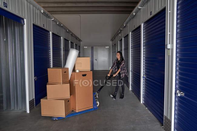 Побічний вид жінки з рухомою тачкою, навантаженою картонними коробками, що організовують склад. — стокове фото