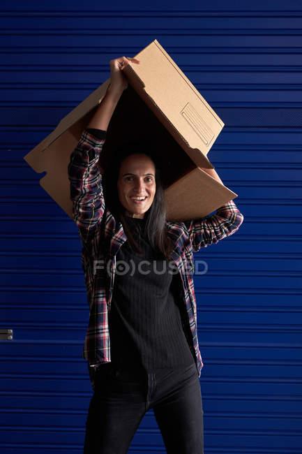 Забавная женщина с коробкой, смотрящая в камеру, как веселится в кладовке — стоковое фото