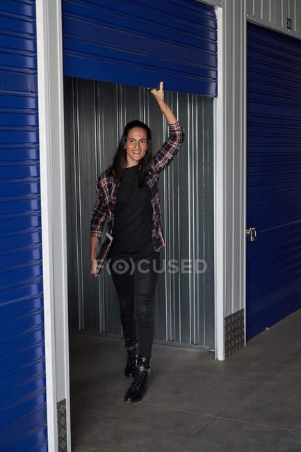 Счастливая случайная женщина в клетчатой рубашке, открывающая дверь самохранения и держащая цифровой планшет — стоковое фото