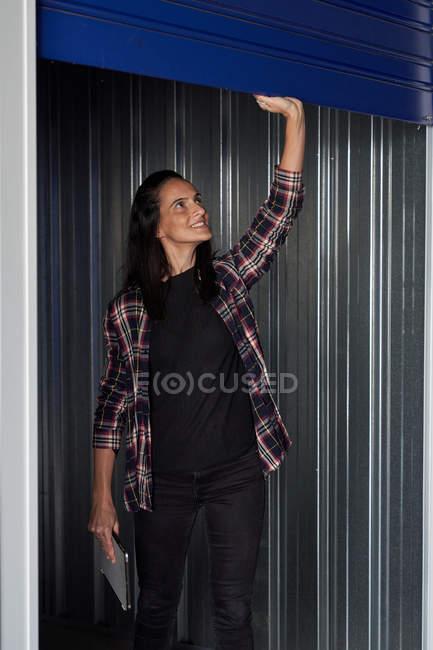 Fröhliche, lässige Frau im karierten Hemd öffnet Selfstorage-Tür und hält digitales Tablet in der Hand — Stockfoto