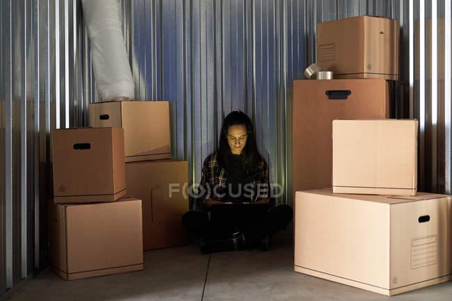 Mujer que utiliza el ordenador portátil como sentada con piernas cruzadas en suelo de hormigón en una sala de autoalmacenamiento llena de cajas de cartón. - foto de stock