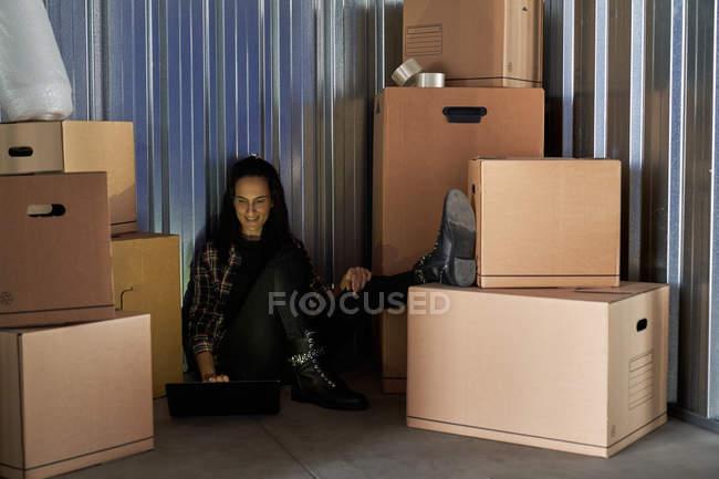 Mujer que utiliza ordenador portátil como sentada en suelo de hormigón en una sala de autoalmacenamiento llena de cajas de cartón. - foto de stock