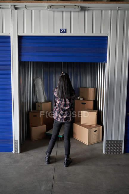 Jeune femme prudente fermeture self stockage salle pleine de boîtes — Photo de stock