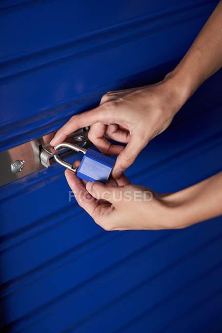 Mains de femme prudente fermeture self stockage porte bleue — Photo de stock