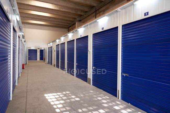 Intérieur du bâtiment de self-stockage industriel à louer avec portes bleues verrouillées — Photo de stock