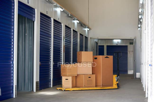 Внутрішнє приміщення промислового самозберігання для оренди з синіми замкненими дверима та картонними коробками. — стокове фото