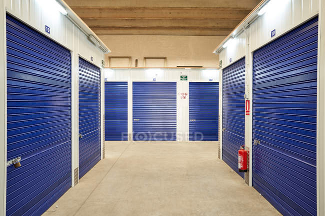 Interior of industrial self storage building for rental with blue locked doors — Stock Photo