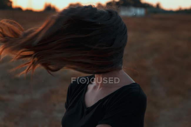 Donna irriconoscibile con viso coperto da lunghi capelli soffiati con forte vento mentre in piedi nel prato in natura — Foto stock