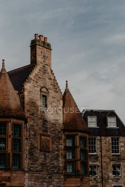 Shabby facade of ancient house with towers and exhaust pipes against cloudy sky in town — Stock Photo