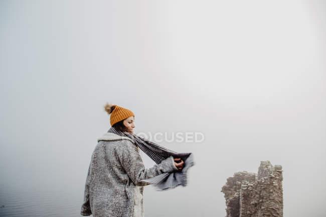 Vista lateral da senhora em roupas quentes andando no parque nebuloso no dia nublado — Fotografia de Stock