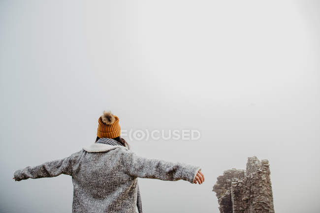 Back view of unrecognizable woman in warm clothes with open arms walking in foggy park on cloudy daytime — Stock Photo
