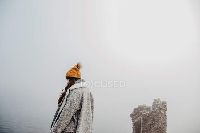 Side view of lady in warm clothes walking in foggy park on cloudy daytime — Stock Photo