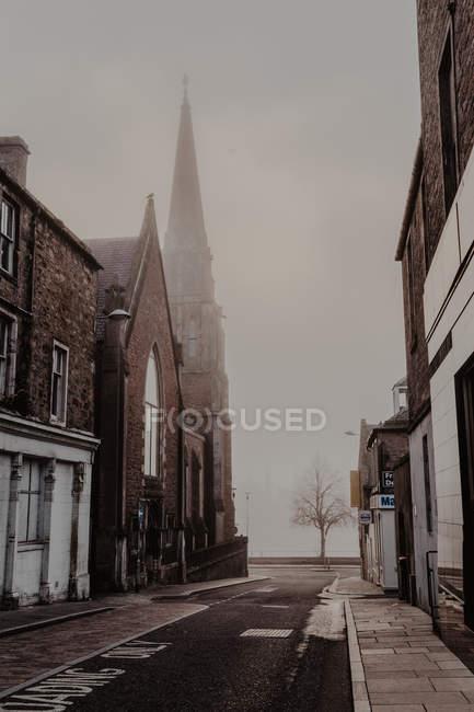 Foggy vecchia strada stretta con case e strada su nuvoloso giorno — Foto stock
