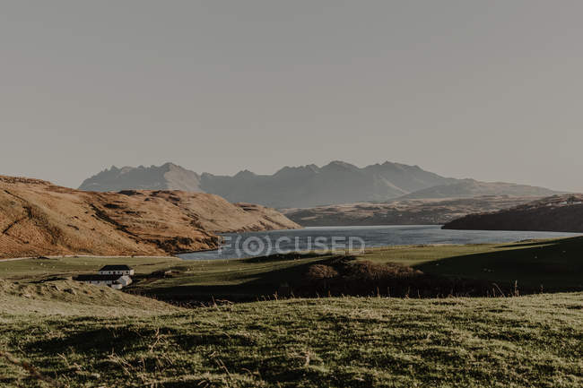 Mountains with rocks and lake against clear blue sky with rays of sunlight landscape of wild nature in fall — Stock Photo
