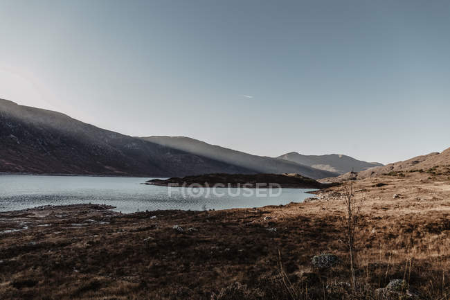 Mountains with rocks and lake against clear blue sky with rays of sunlight in landscape of wild nature in fall — Stock Photo