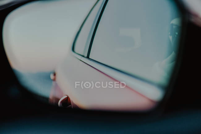 Red automobile reflected in rear view mirror during driving on road on sunny daytime — Stock Photo