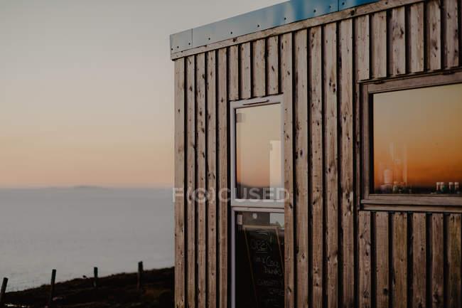 Café en bois compact avec grandes fenêtres et marqueur avec menu donnant sur les montagnes à la lumière du coucher du soleil — Photo de stock