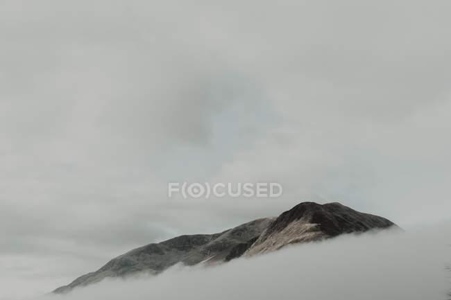 Einsame Gipfel umgeben von Wolken unter grauem Himmel bei nebligem Tag — Stockfoto