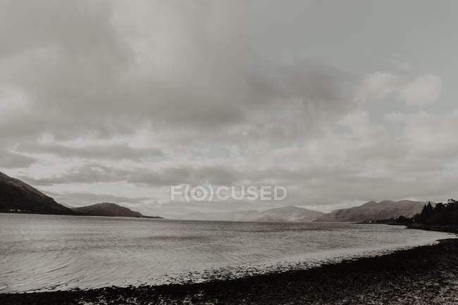 Vuoto acqua ondulata lavaggio riva scura circondato da montagne sotto cielo grigio nuvoloso — Foto stock