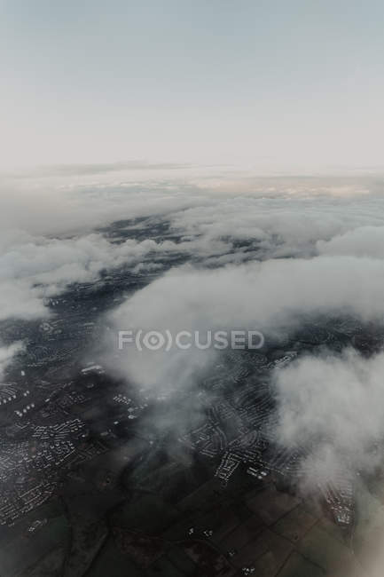 From above aerial view of densely populated city with streets and houses hidden behind white clouds — Stock Photo