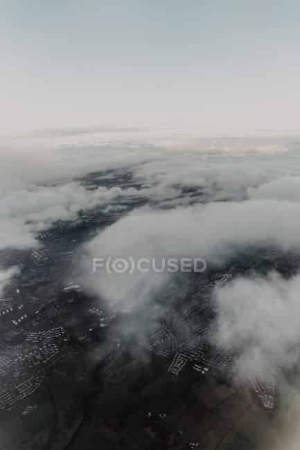 Dall'alto vista aerea della città densamente popolata con strade e case nascoste dietro nuvole bianche — Foto stock