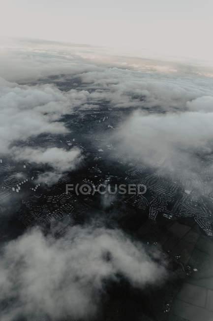 Vista aérea desde arriba de la ciudad densamente poblada con calles y casas escondidas detrás de nubes blancas - foto de stock