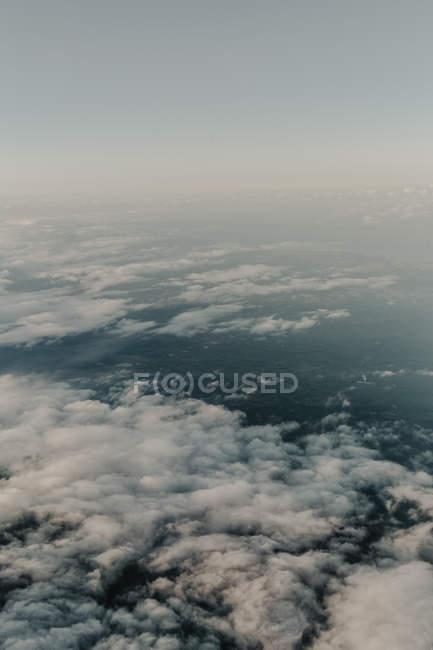 D'en haut des nuages blancs dans le ciel au-dessus du paysage sombre — Photo de stock